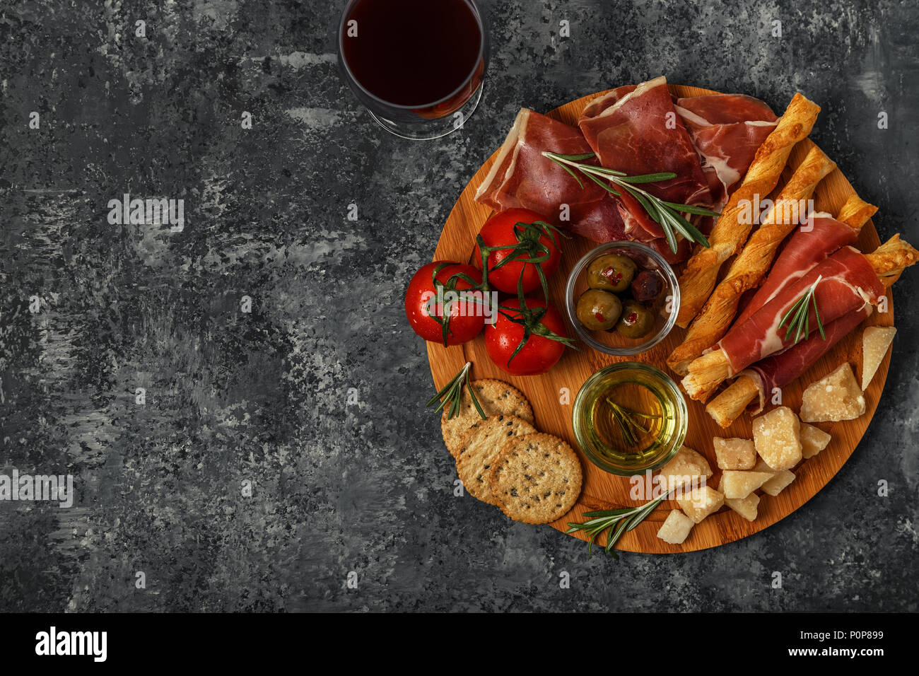 Cheese and meat appetizer selection. Prosciutto, parmesan, bread sticks, olives, tomatoes on wooden board, top view. - Stock Image