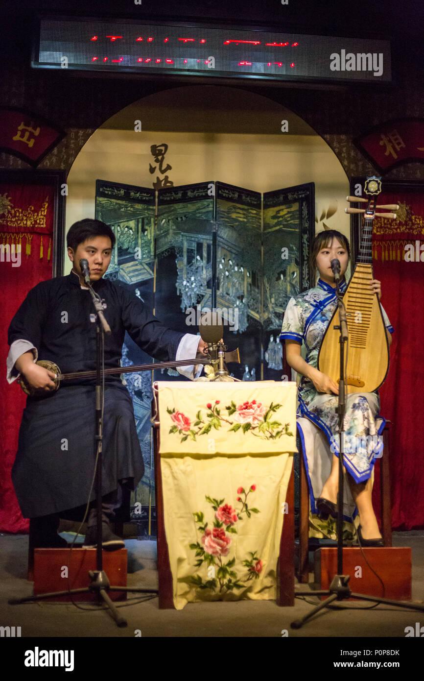 Suzhou, Jiangsu, China. Duet Playing Traditional Instruments: Woman on Pipa, Man on 'Three Strings.' - Stock Image