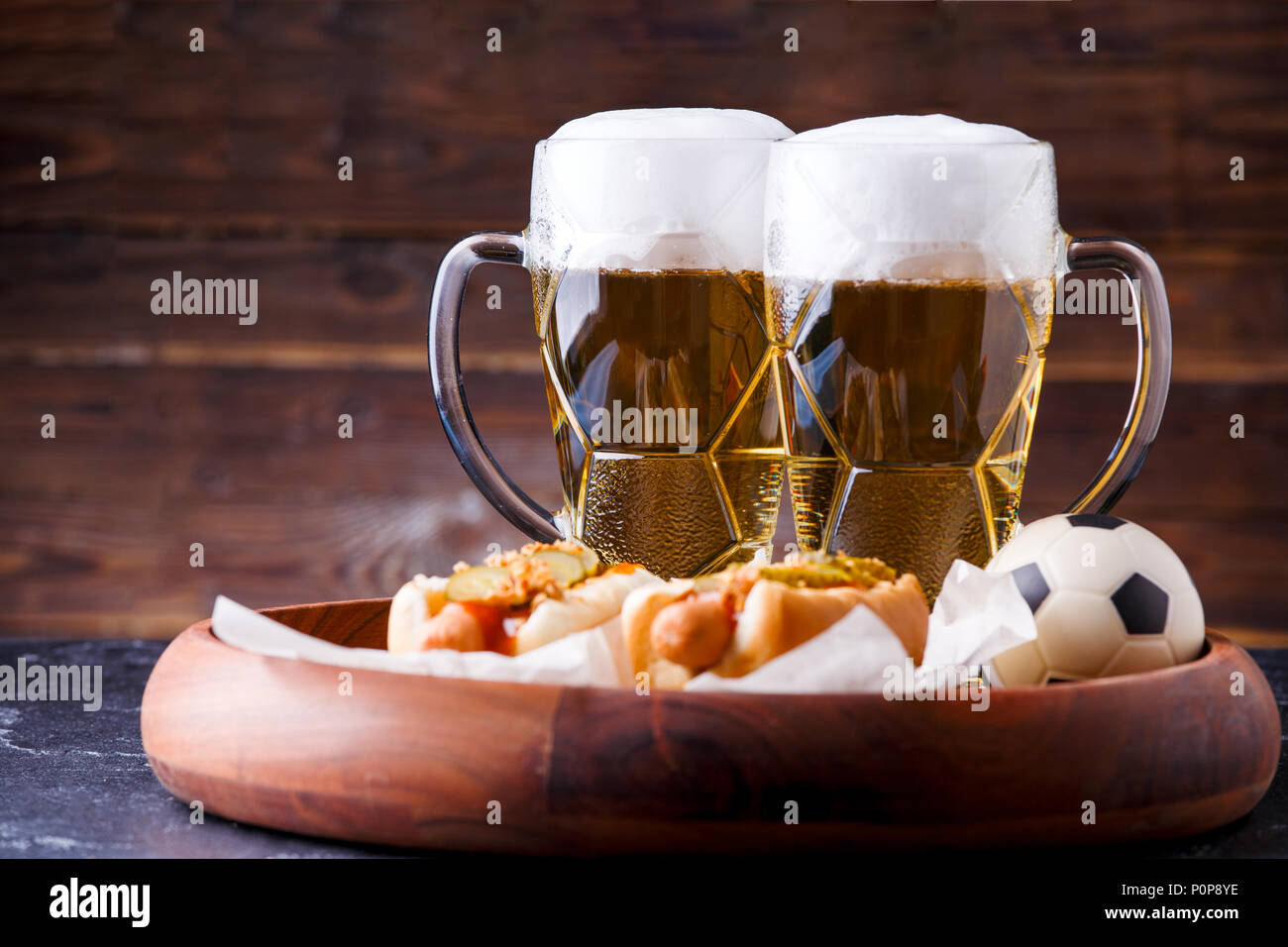 Photo of two mugs of beer and hot dogs on wooden tray with football Stock Photo