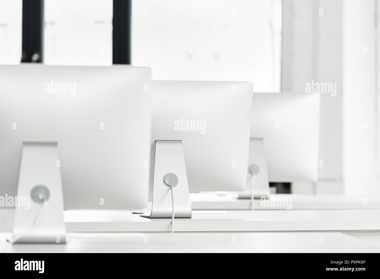 close up view of white computer monitors standing on tables in computer class - Stock Image