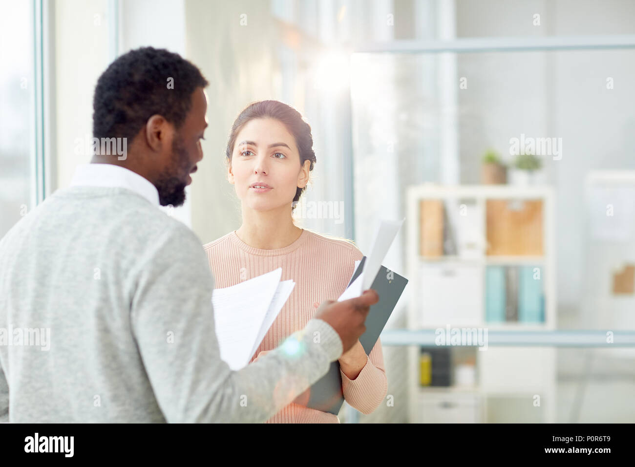 Bearded African American entrepreneur studying statistic data with young subordinate while standing at modern open plan office, lens flare - Stock Image