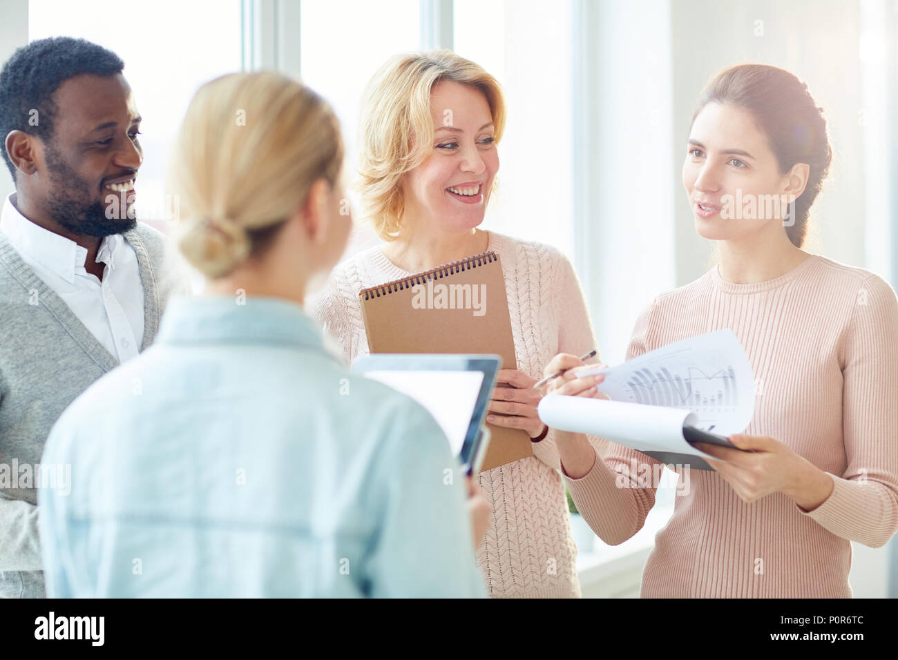 Multi-ethnic group of white collar workers enjoying each others company while having informal working meeting at open plan office - Stock Image