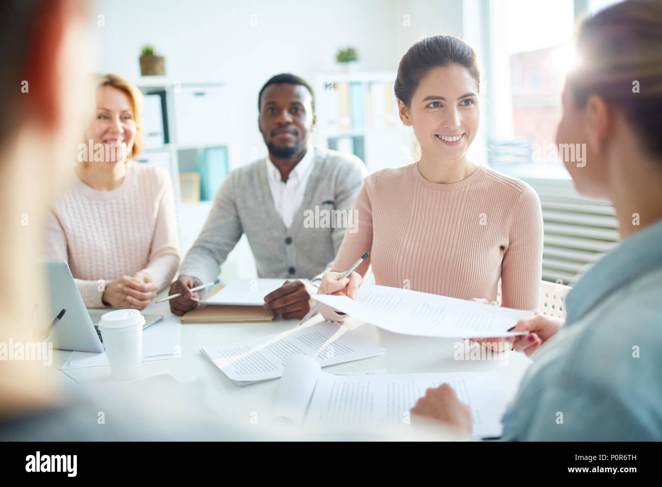Joyful multi-ethnic team of white collar workers having productive project discussion while gathered together at modern open plan office, lens flare - Stock Image
