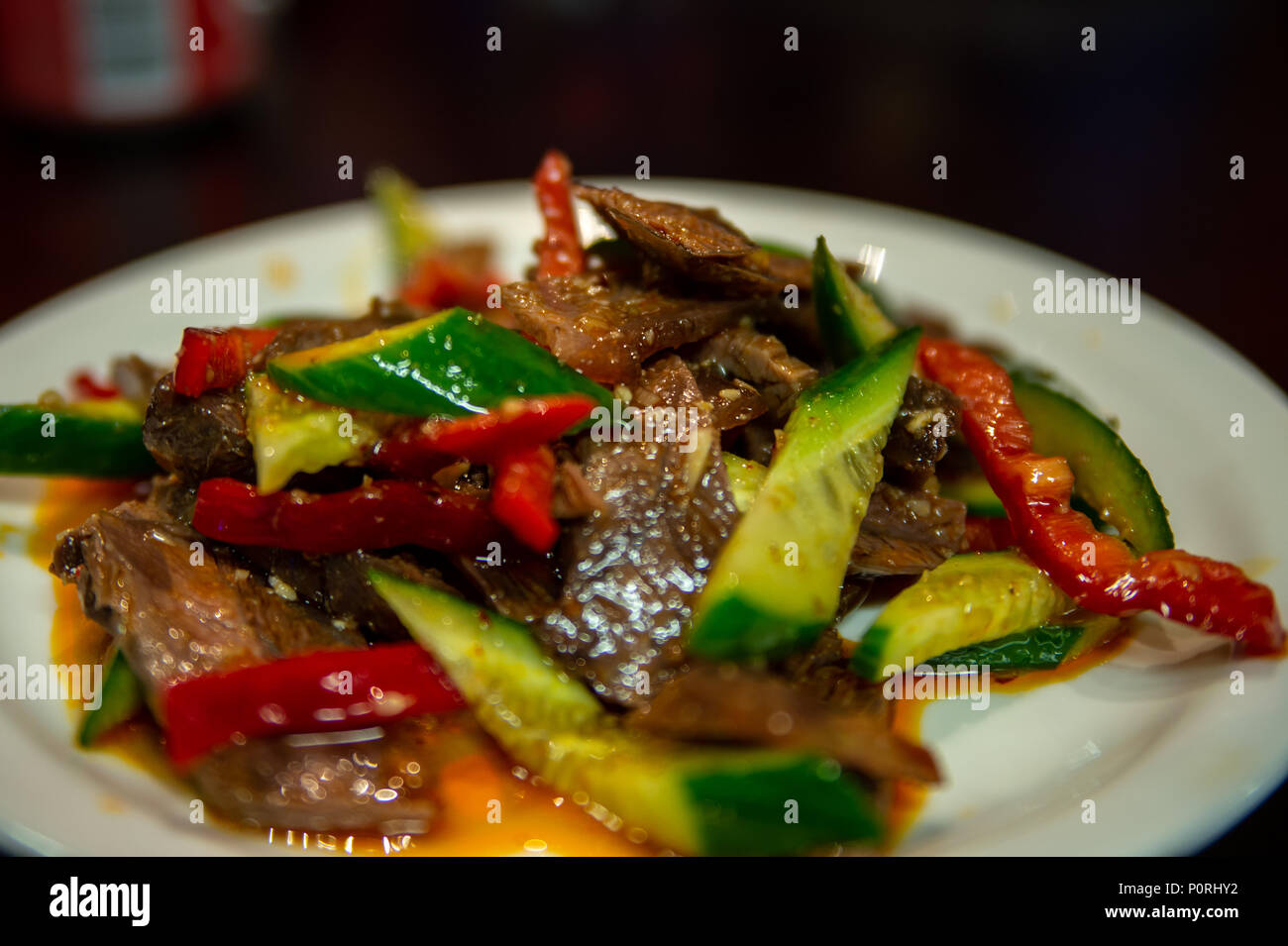 Uyghur Cuisine: beef salad, sliced beef with fresh cucumber, red peppers and chili oil - Stock Image