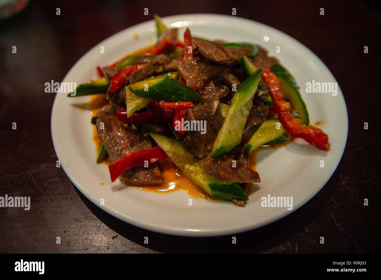 Uyghur Cuisine: beef salad, sliced beef with fresh cucumber, red peppers and chili oil Stock Photo