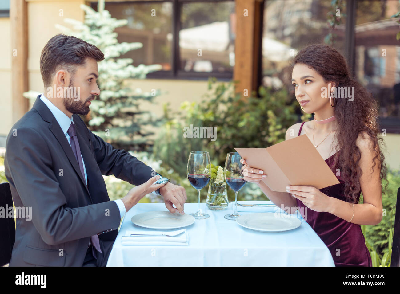 Couple having romantic date in restaurant, woman choosing meal in menu, man looking at watches Stock Photo