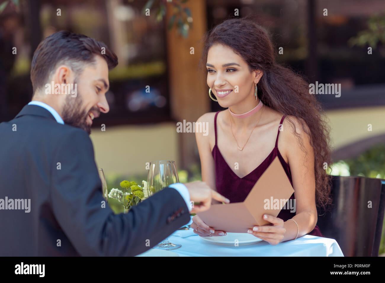 Couple having romantic date in restaurant, choosing meal in menu Stock Photo