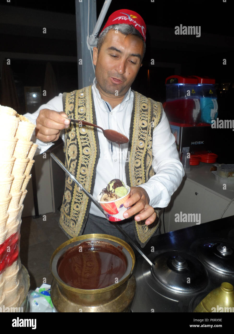 An Ice cream vendor wearing traditional Turkish yelek, waistcoat or vest, while pouring melted chocolate over the ice cream. - Stock Image
