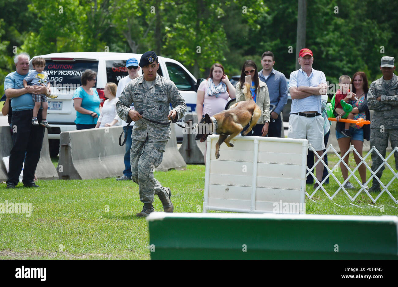U.S. Air Force Senior Airman Trey Weston, 628th Security Forces Squadron military working dog handler, runs through an obstacle course with Ari, MWD, during a base picnic at the Air Base Picnic Grounds May 5, 2017, at Joint Base Charleston, S.C. Attendees were provided free meals were and able to participate in various activities including face painting, wall rock climbing, live music and a Military Working Dog demonstration. Stock Photo