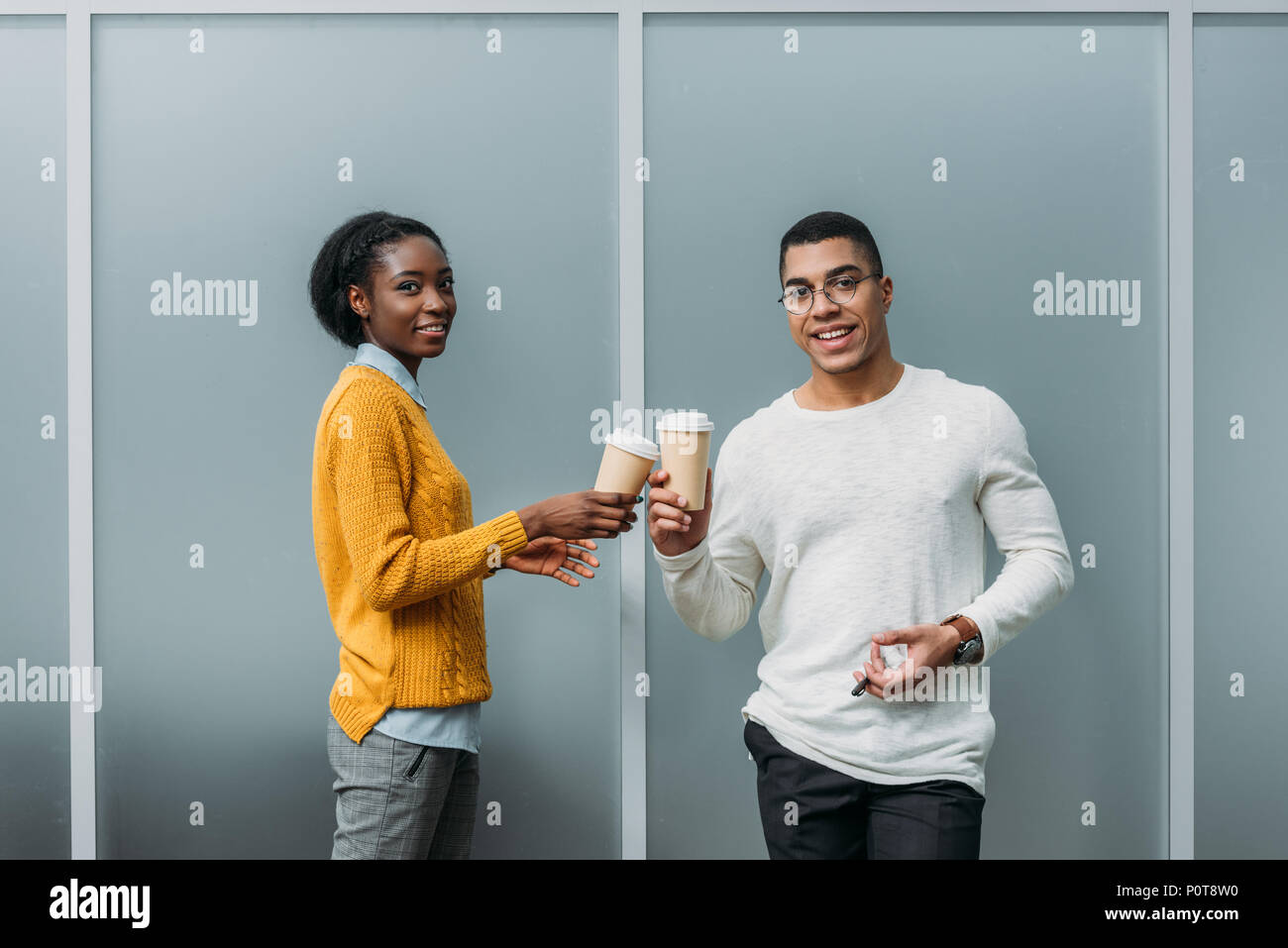 young african american business partners clinking disposable cups of coffee - Stock Image