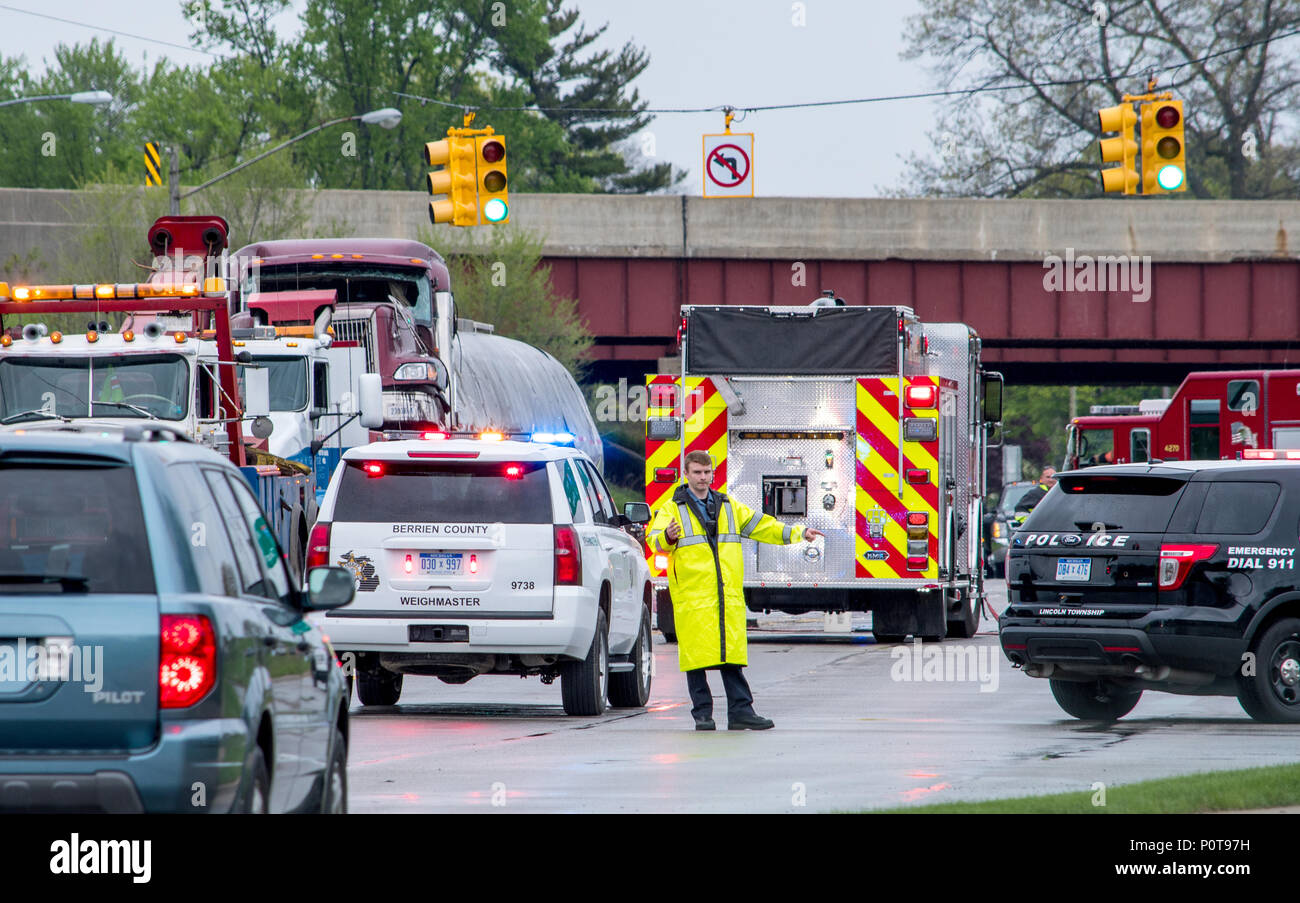 May 18 2018 Stevensville MI USA;  A police officer in rain gear directs traffic at the scene of a bad accident Stock Photo