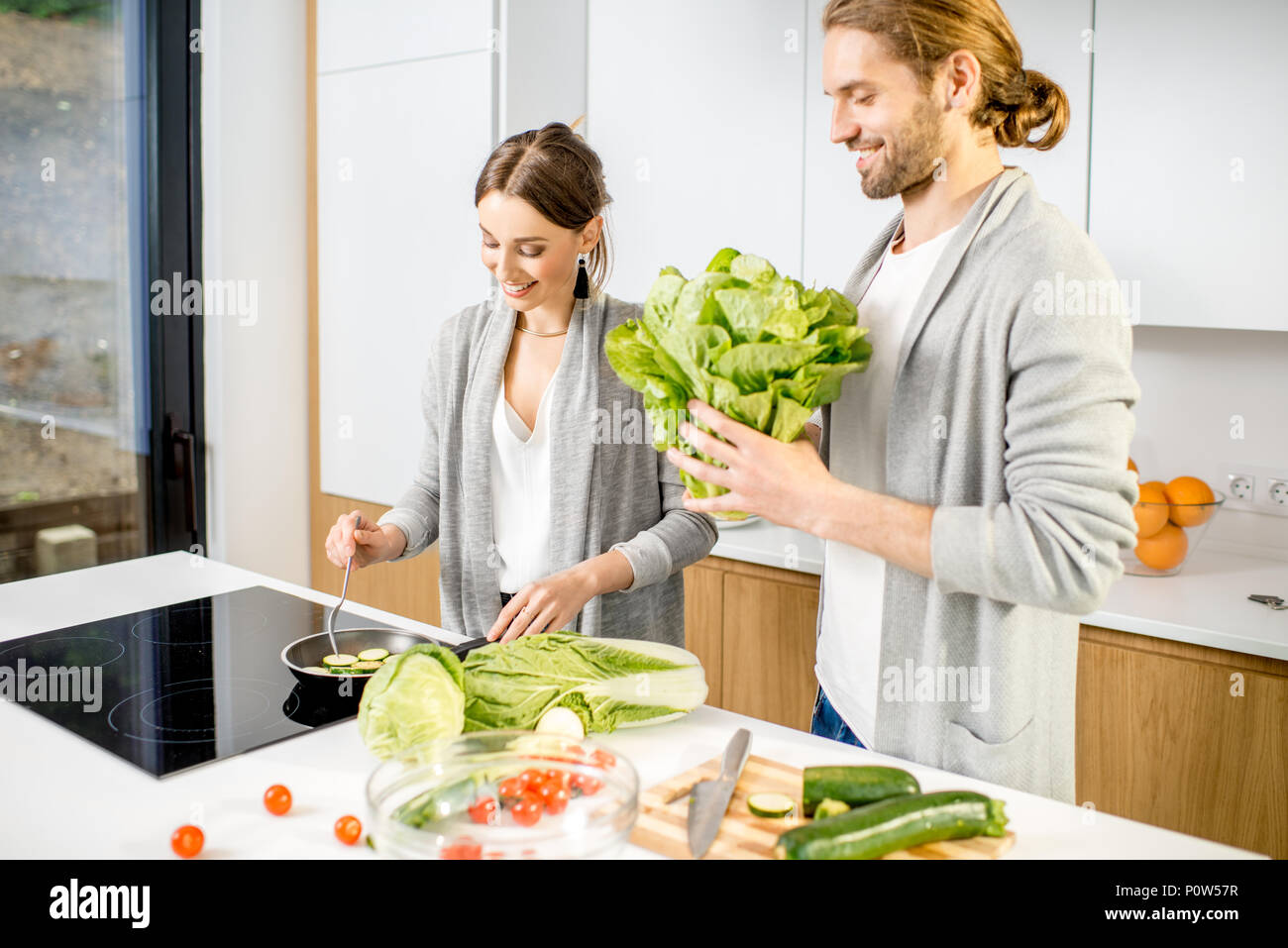 Couple cooking food at the kitchen home - Stock Image