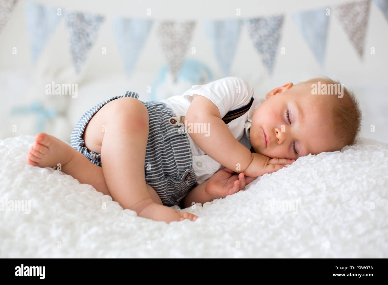 Sweet Little Child Baby Boy Sleeping In A Sunny Bedroom During The Day Having A Rest Flag Banner Decoration On The Wall Behind Him Stock Photo Alamy