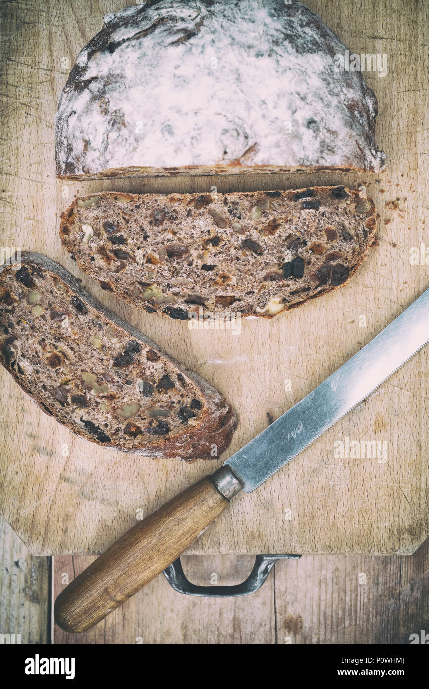 Organic fruit sourdough loaf with bread knife on a wooden board. UK. Vintage filter applied - Stock Image