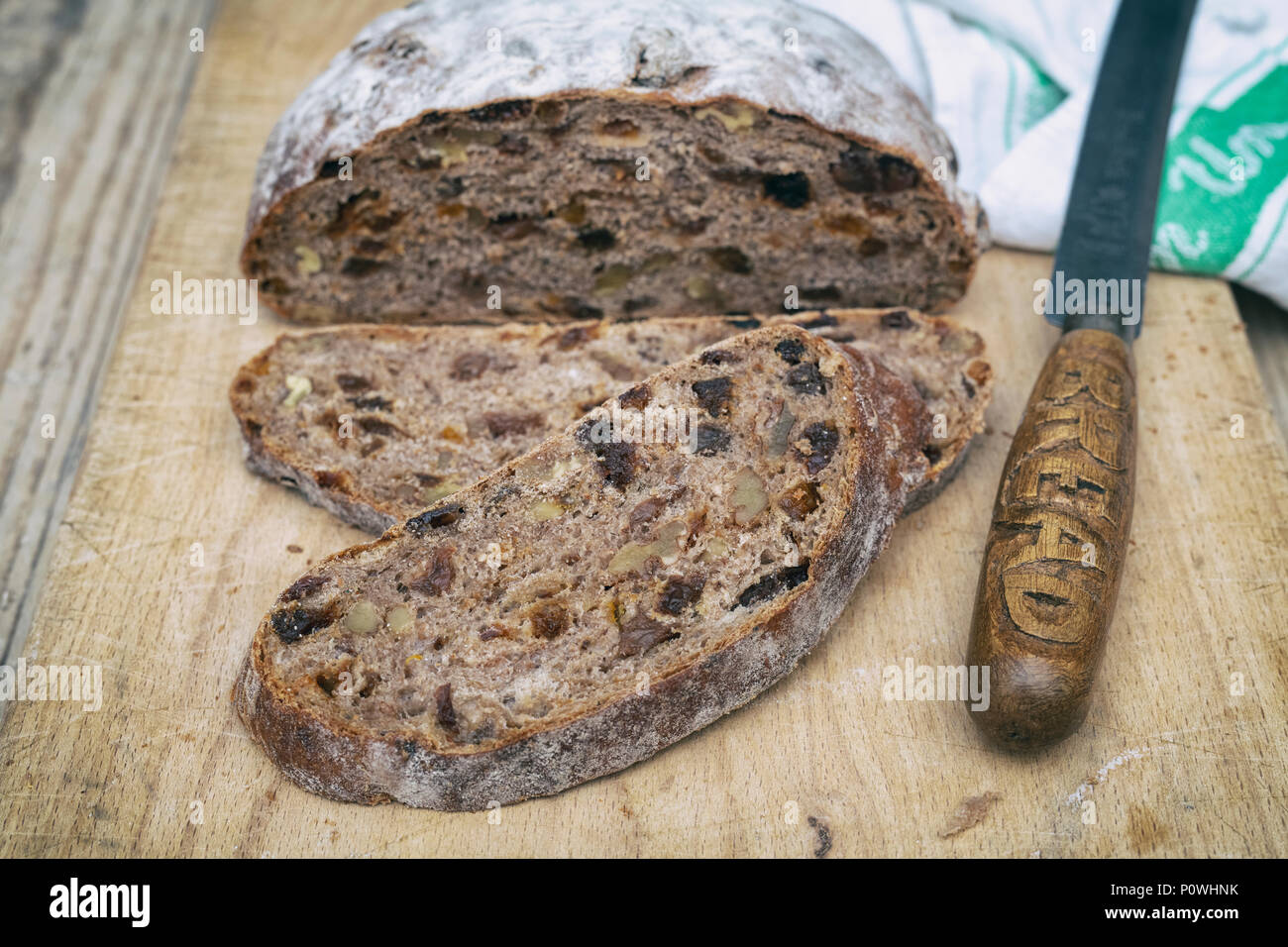 Organic fruit sourdough loaf with bread knife on a wooden board. UK. Vintage filter applied Stock Photo