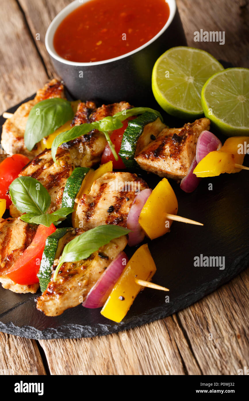 spicy grilled chicken kebabs with vegetables served with ketchup close-up on the table. vertical - Stock Image