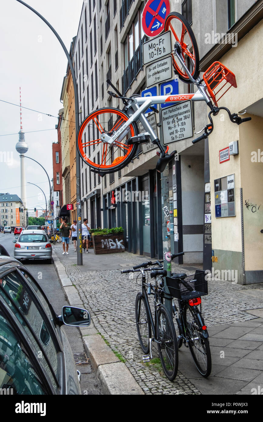 Berlin Mitte. Bike suspended on traffic sign pole possibly as pedestrian objection to clutter of hire bikes on pavements - Stock Image