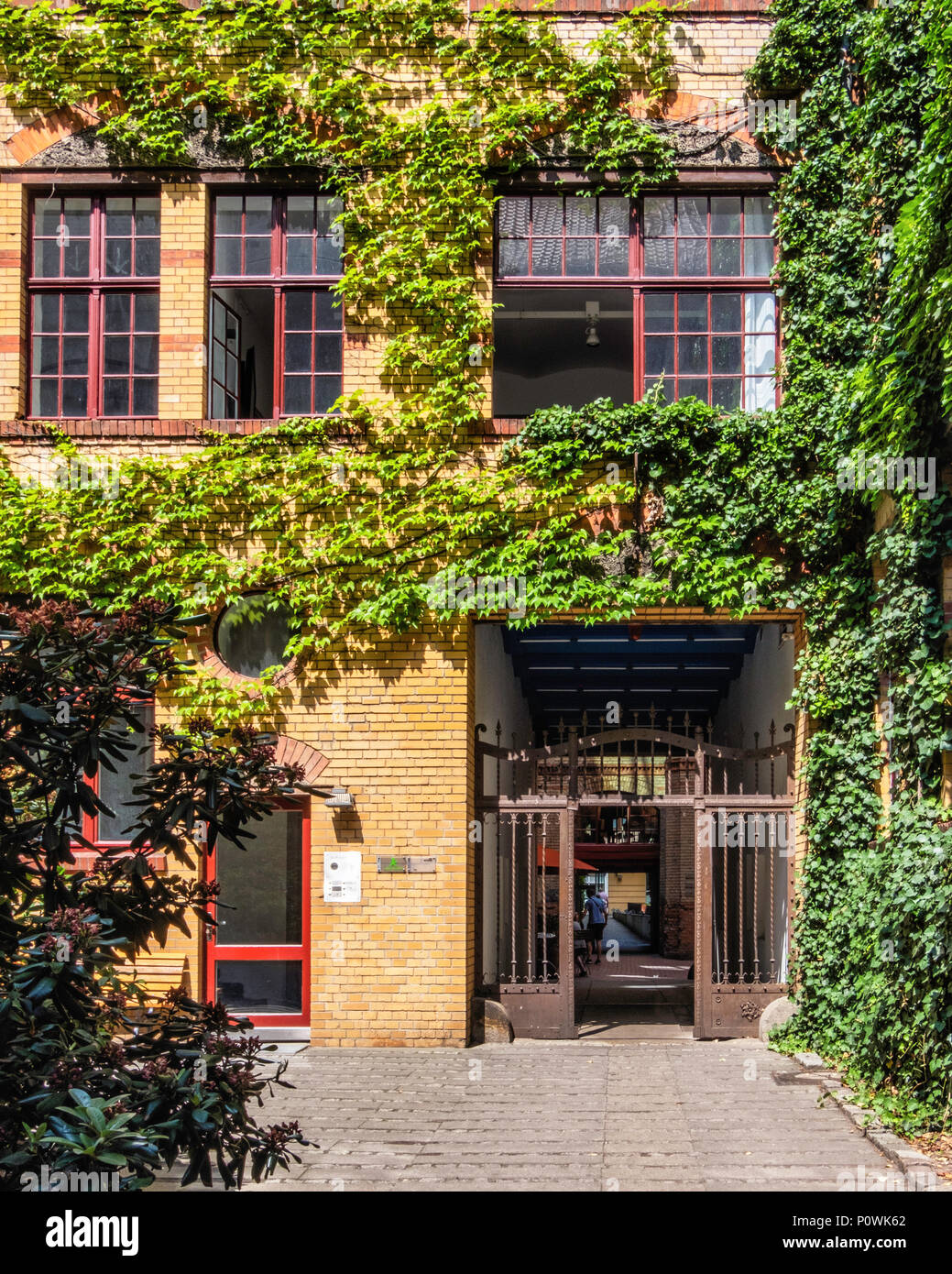 Berlin, Mitte Sophie-Gips-Höfe,Inner couryard, metal gates and ivy covered brick buiding of Historic 19th century former factory.                      - Stock Image