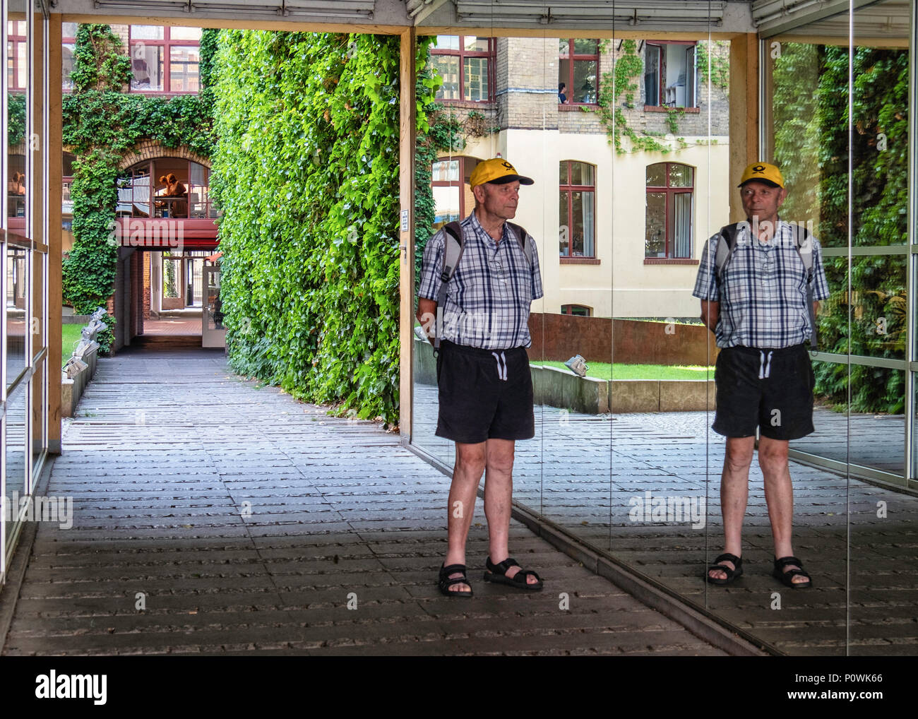 Berlin, Mitte Sophie-Gips-Höfe,Senior man in mirrored entrance of Historic 19th century former factory building courtyard - Stock Image