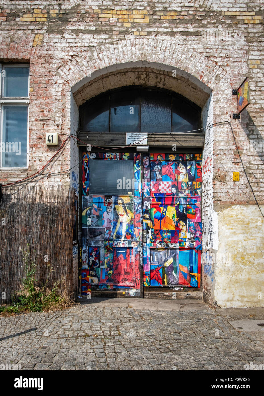 Berlin, Mitte, Oranienburger Straße 41. Colourful Entrance of old building with protected monument statue is home to the 'Ghost wall' legend  The Ghos - Stock Image