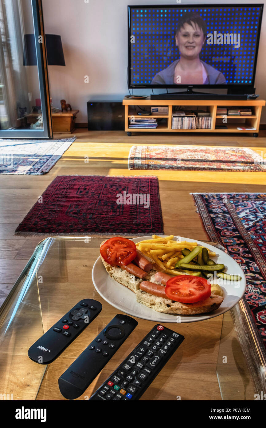 Informal supper, TV dinner, Designer Hotdog on olive bread with chips,mustard,tomatoes and pickled cucumbers - Stock Image