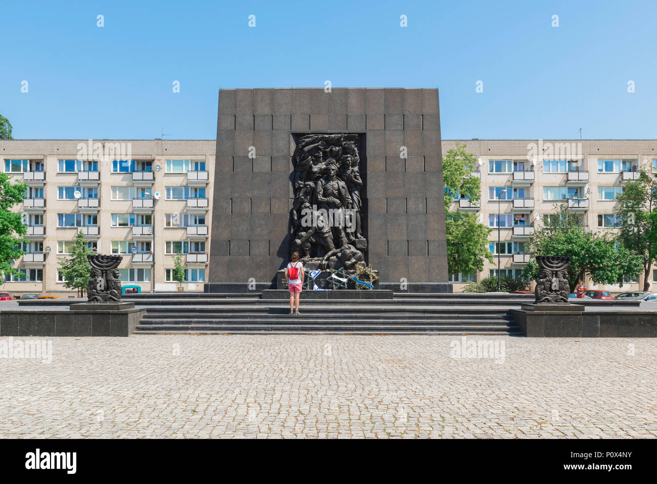 A young woman visits the Ghetto Heroes Monument which commemorates the Warsaw Jewish Ghetto Uprising of 1943, Poland. - Stock Image