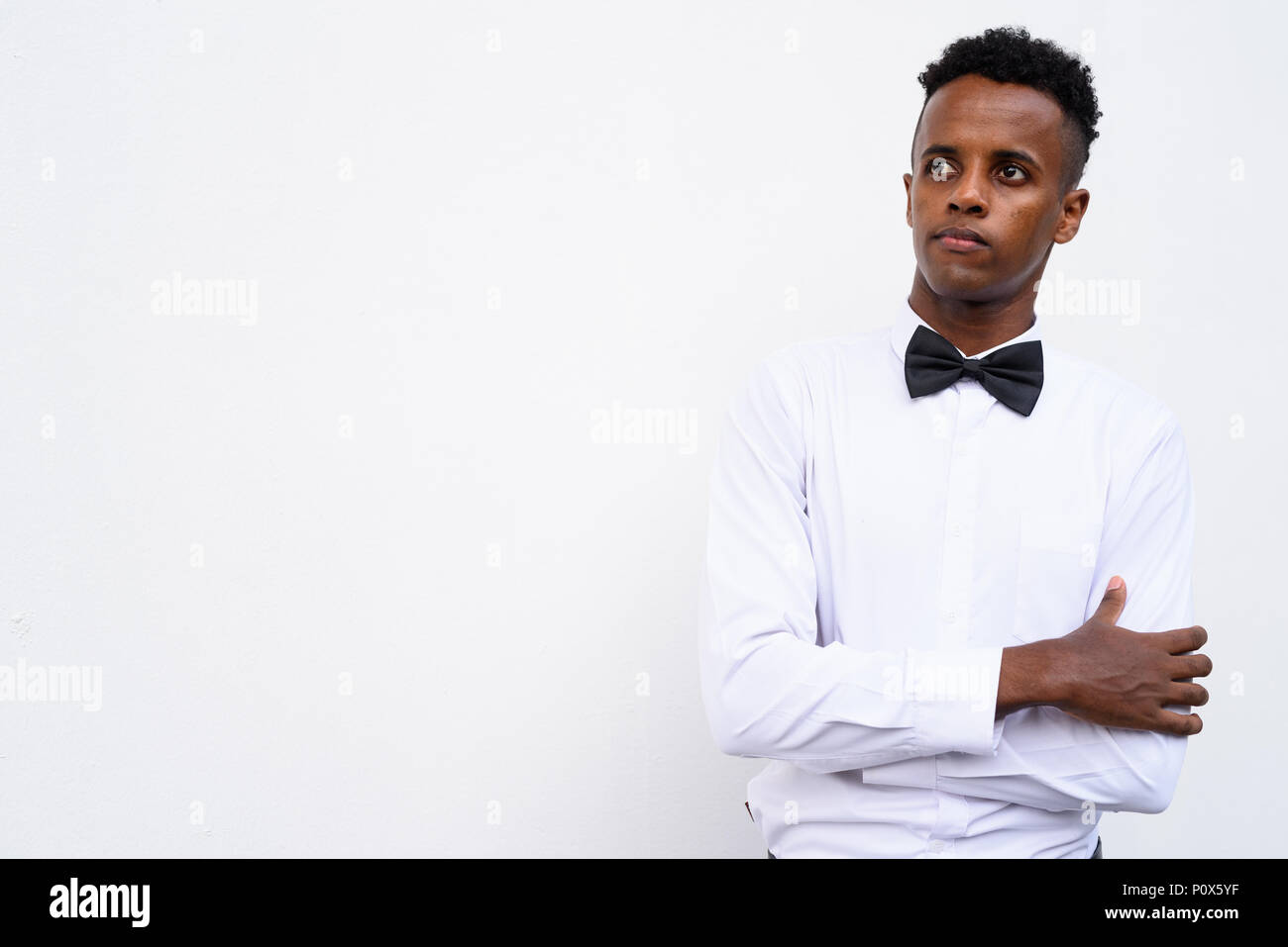 Young handsome African businessman wearing bow tie against white - Stock Image