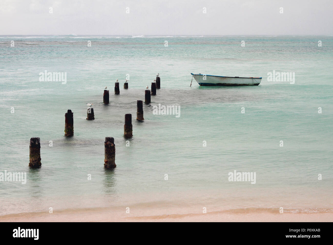 Support of destroyed pier, boat and ocean. Anse de Sent An, Pointe-a-Pitre, Guadeloupe - Stock Image
