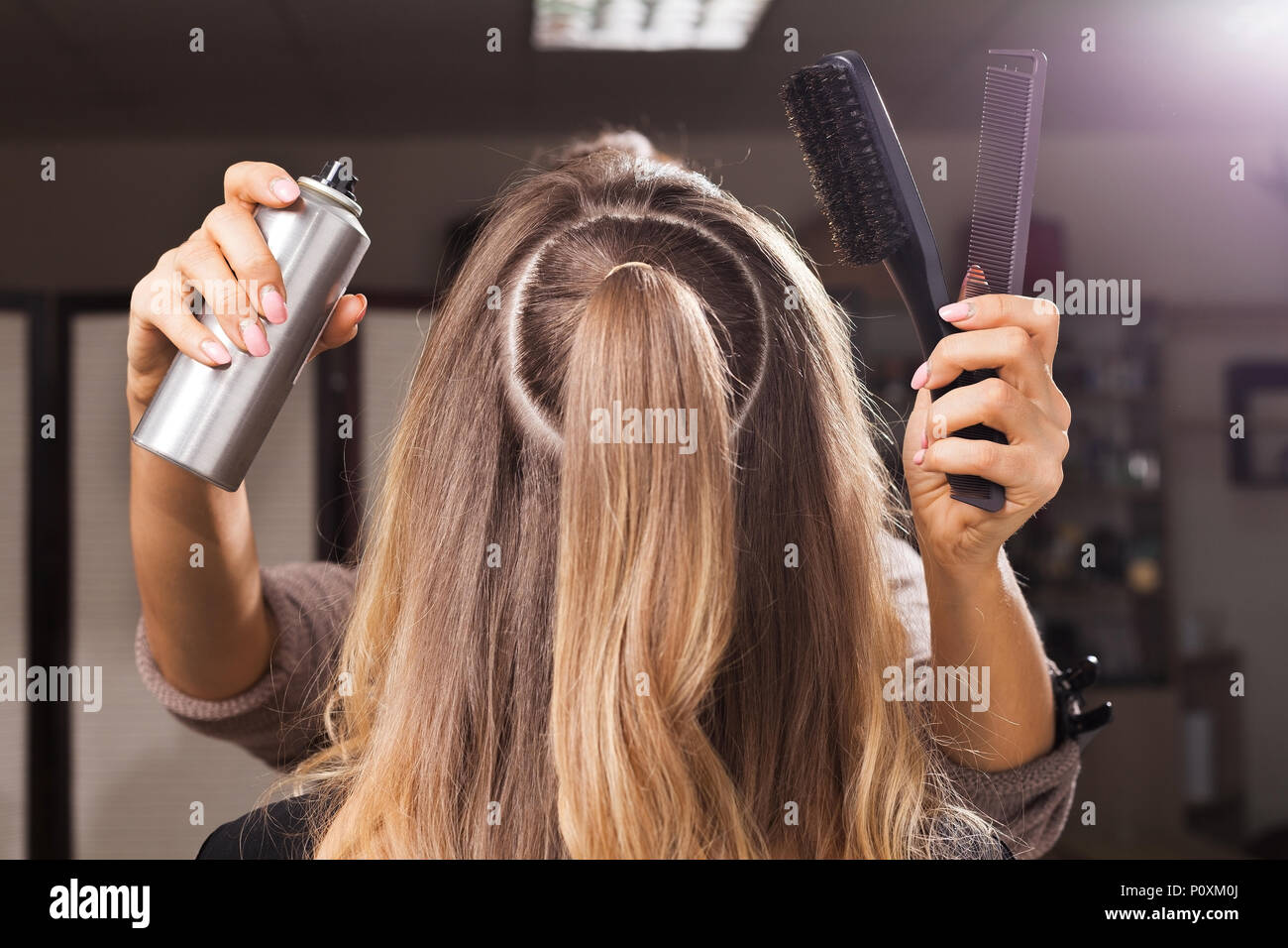 hairdresser fixing hairdo of a model with a hair spray - Stock Image