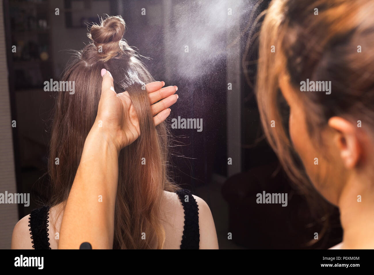 hairdresser fixing hair of a model with a hairspray - Stock Image