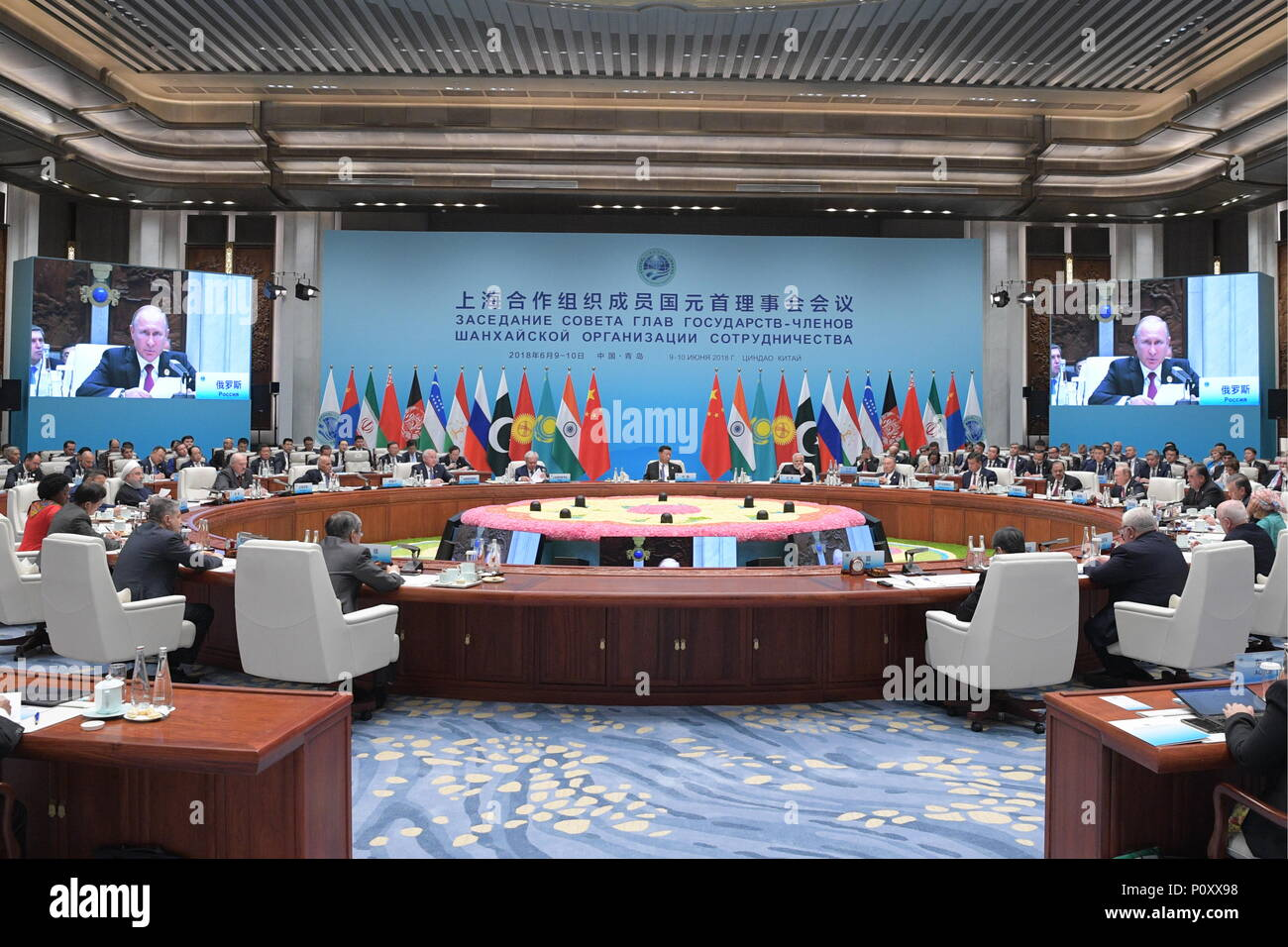QINGDAO, CHINA - JUNE 10, 2018: (from left back at the table clockwise) The President of Iran Hassan Rouhani, the President of Belarus Alexander Lukashenko, the President of Afghanistan Ashraf Ghani, an unidentified official, the SCO Secretary-General Rashid Alimov, the President of the People's Republic of China Xi Jinping, the Prime Minister of India Narendra Modi, the President of Kazakhstan Nursultan Nazarbayev, the President of Kyrgyzstan Sooronbai Jeenbekov (Sooronbay Zheenbekov), the President of Pakistan Mamnoon Hussain, the President of Russia Vladimir Putin, and the President of Taji - Stock Image