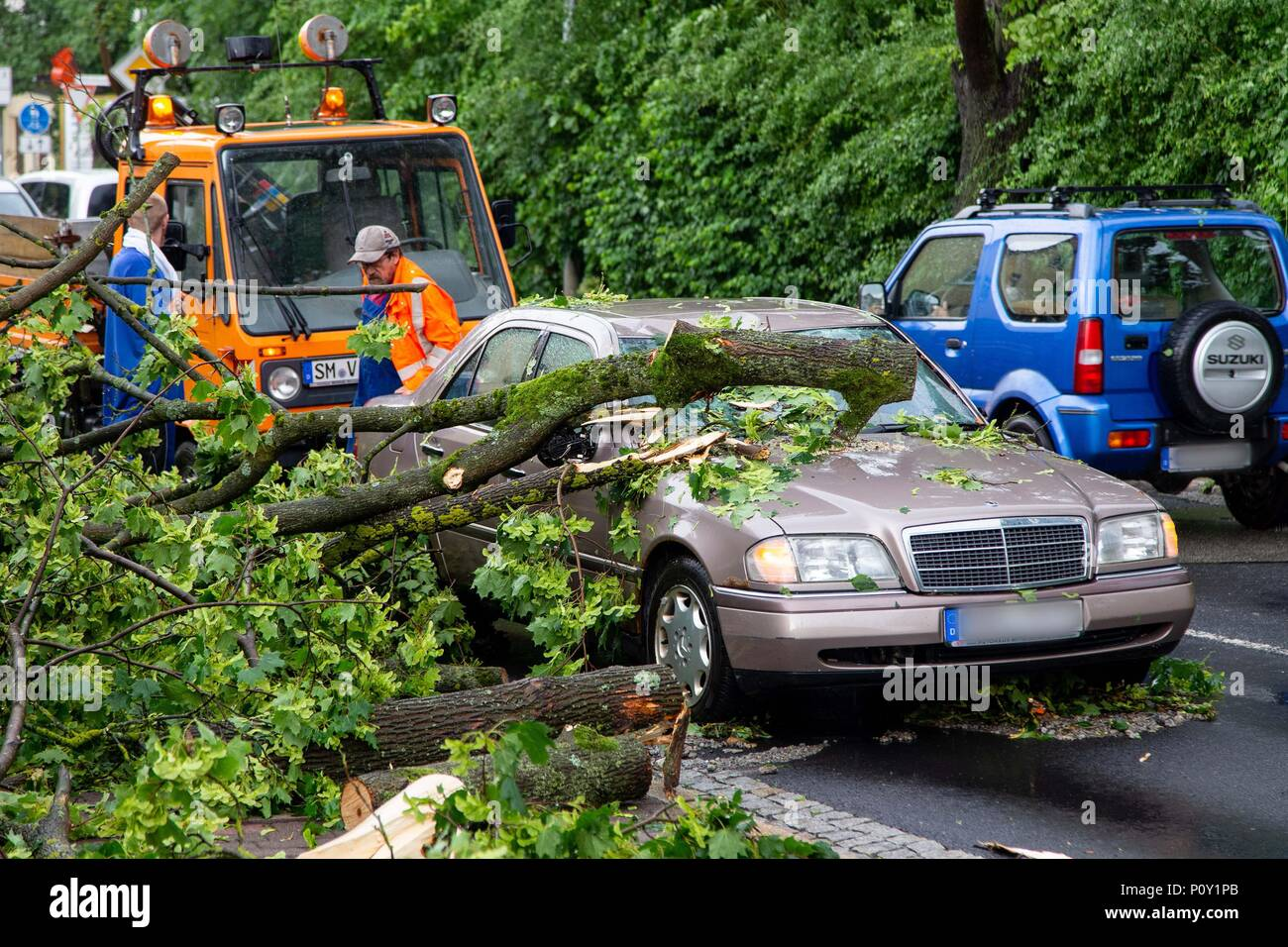 9 June 2018, Meiningen, Germany: Fire fighters clear away uprooted trees which have crushed a car. Heavy rainfall and tempestous winds have caused floodings in several Thuringian districts. Especially affected was Schmalkalden-Meiningen, as the police informed. Photo: Ittig/NEWS5/dpa - ACHTUNG: Autokennzeichen gepixelt - Stock Image