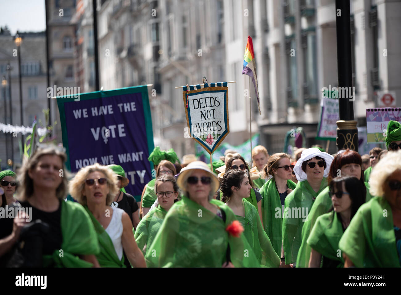 Women marching through London to mark 100 years since the first British women won the vote. Women donned the colours of the suffragette movement - green, white and purple - as part of a mass procession. - Stock Image