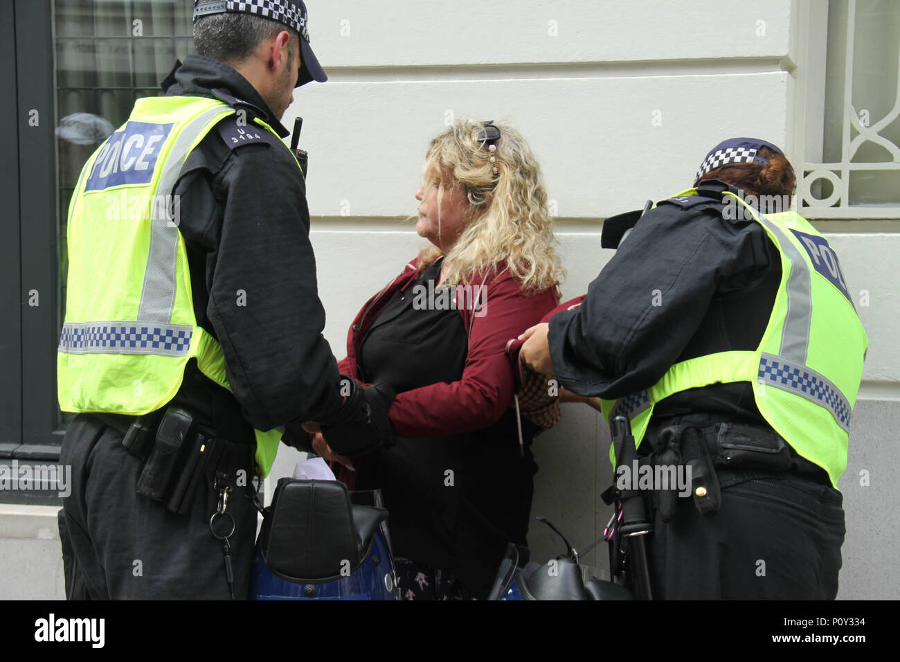 London, UK - 10 June 2018: A woman is searched and questioned by police officers during the demonstration outside the Saudi Arabia Embassy for Al Quds Day on 10 June 2018. The annual event held on the last Friday of Ramadan that was initiated in 1979 to express support for the Palestinians and oppose Zionism and Israel. Credit: David Mbiyu - Stock Image