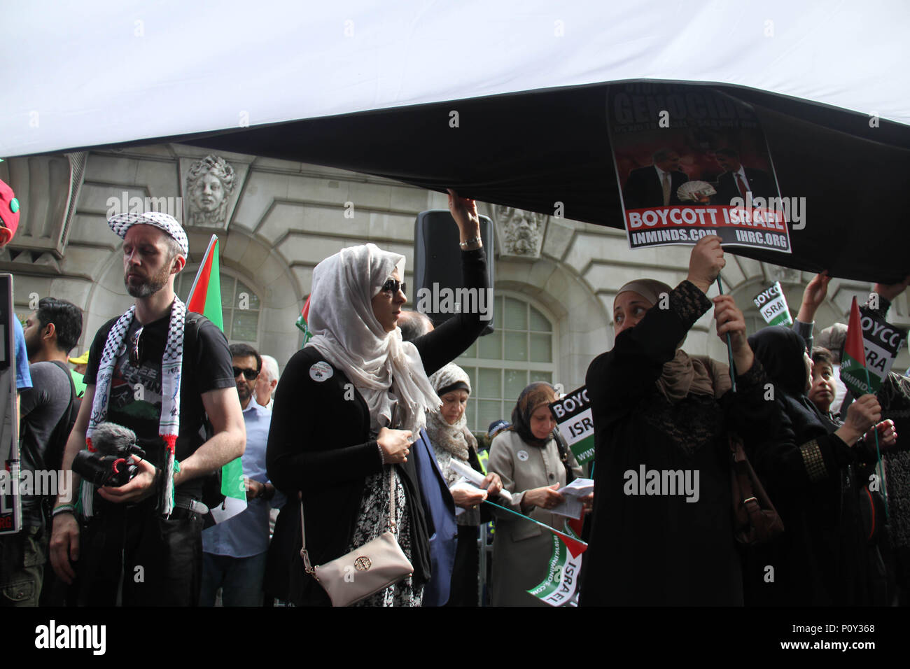 London, UK - 10 June 2018: Protestors seen below a Palesitine flag take part  in a demonstration outside the Saudi Arabia Embassy for Al Quds Day on 10 June 2018. The annual event held on the last Friday of Ramadan that was initiated in 1979 to express support for the Palestinians and oppose Zionism and Israel. Credit: David Mbiyu Credit: david mbiyu/Alamy Live News - Stock Image