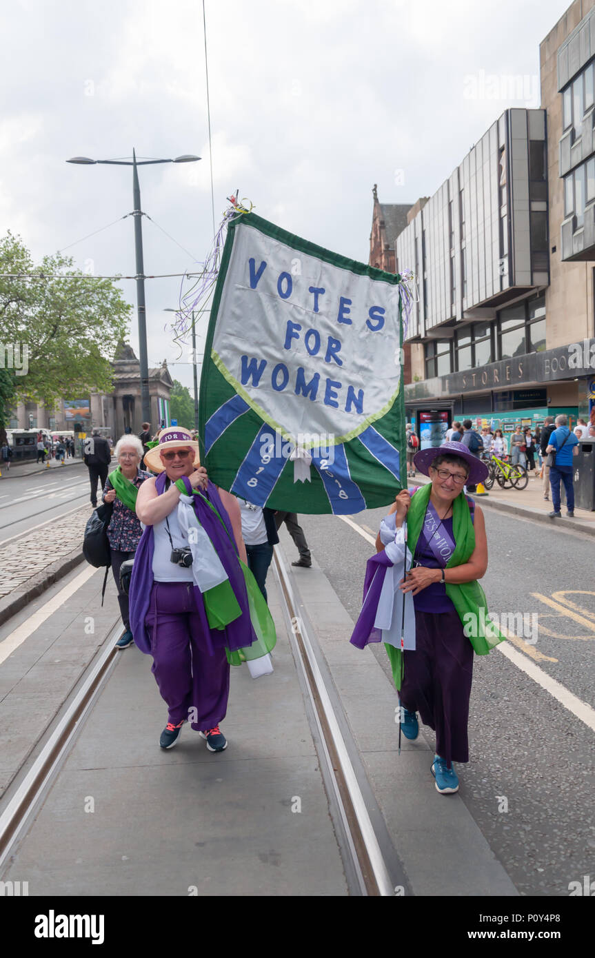Edinburgh, Scotland, UK. 10th June, 2018. Marchers carrying a banner that says Votes For Women during the Edinburgh Processions Artwork march celebrating 100 years since British women won the right to vote. Thousands of women came together in the four capitals of the UK,  Belfast, Cardiff, Edinburgh and London. The Participants wore either a green, white or violet scarf and walked in stripes through the city streets to depict the colours of the suffragettes. Credit: Skully/Alamy Live News - Stock Image