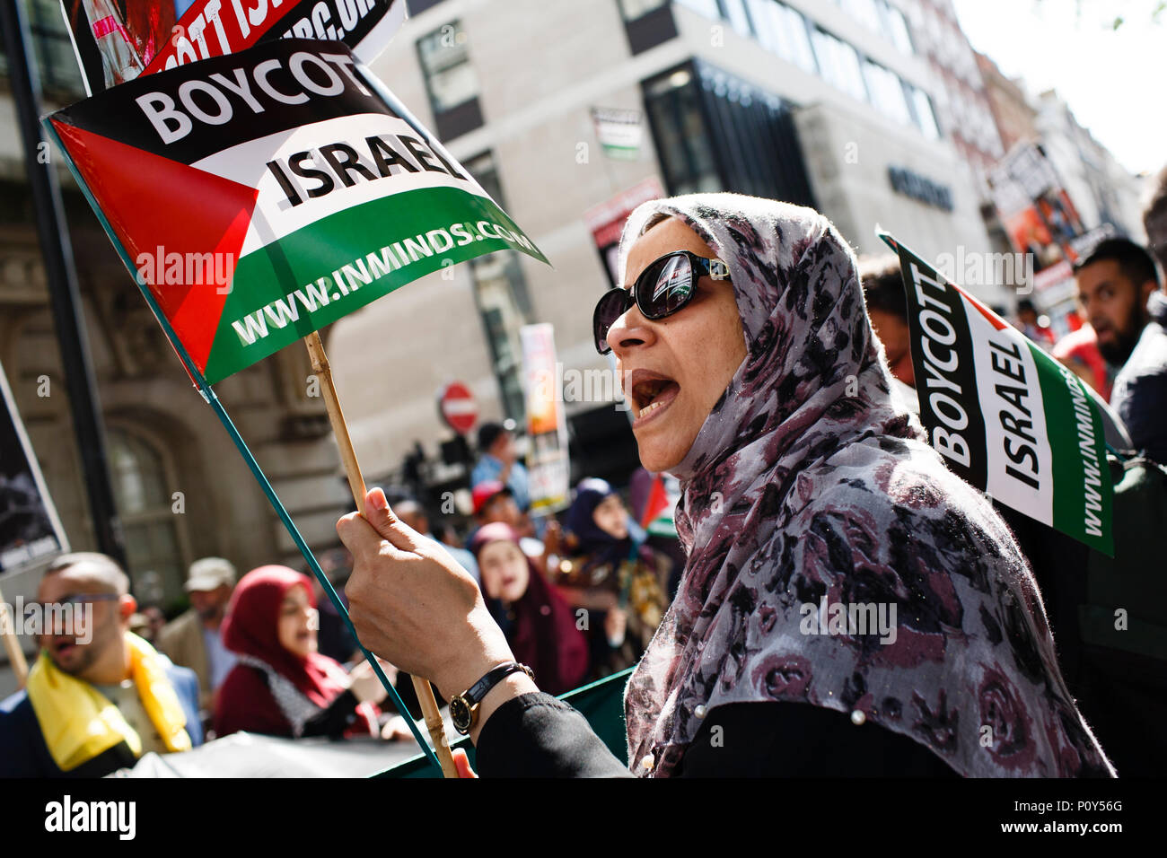 A woman holds a 'Boycott Israel' flag during the annual pro-Palestine/anti-Israel Al Quds Day demonstration in central London. The demonstration is notably controversial in the city for the flying of Hizbullah flags that typically takes place during the course of it. - Stock Image