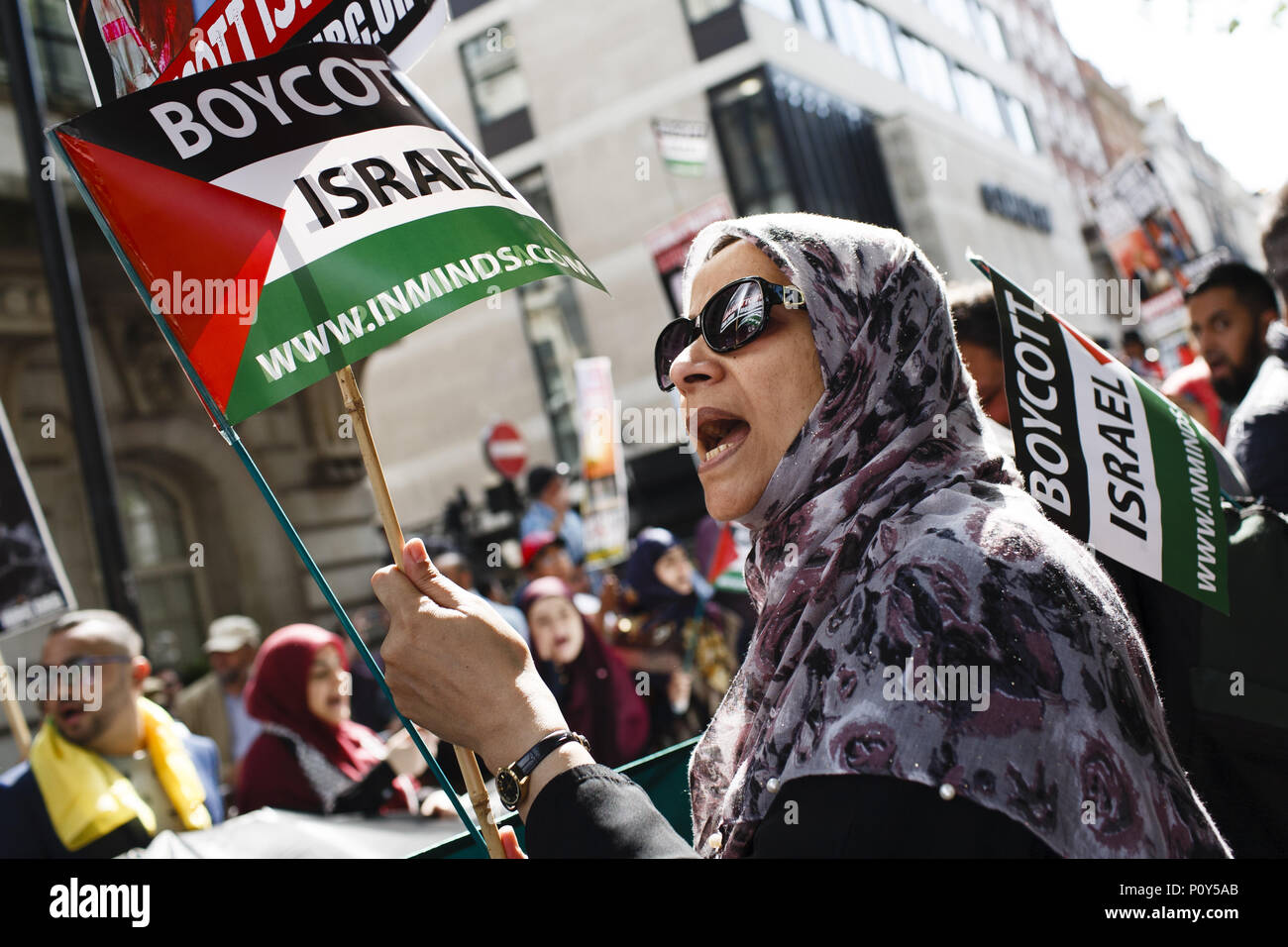 London, UK. 10th June, 2018. A woman holds a 'Boycott Israel' flag during the annual pro-Palestine/anti-Israel Al Quds Day demonstration in central London. The demonstration is notably controversial in the city for the flying of Hizbullah flags that typically takes place during the course of it. Credit: David Cliff/SOPA Images/ZUMA Wire/Alamy Live News - Stock Image