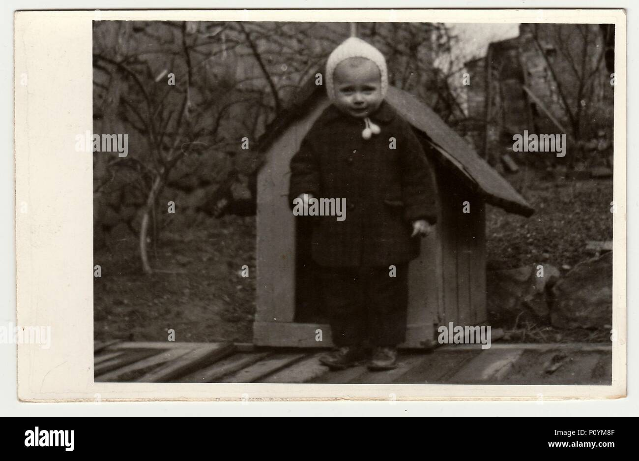 THE CZECHOSLOVAK REPUBLIC, CIRCA 1942: Vintage photo shows a small girl and kannel (doghouse), circa 1942. Stock Photo