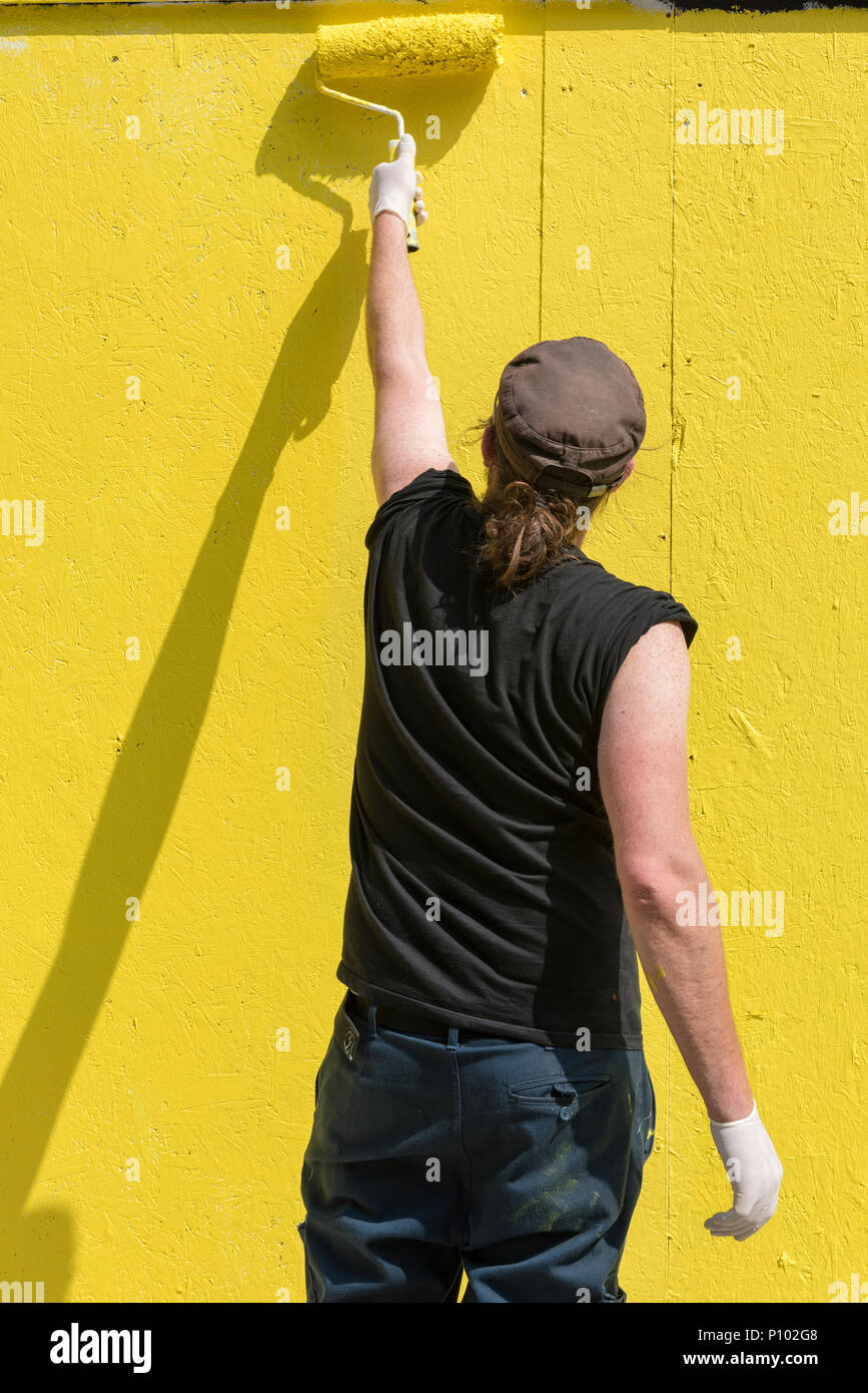 a man wearing black clothes and a baseball cap using a roller to paint the side of a building or a wall in a bright yellow paint. painting a wall. - Stock Image