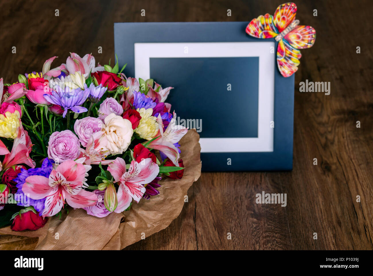 beautiful bouquet with different colors and photo frame on a wooden background. Colorful bouquet of different fresh flowers, close-up Stock Photo