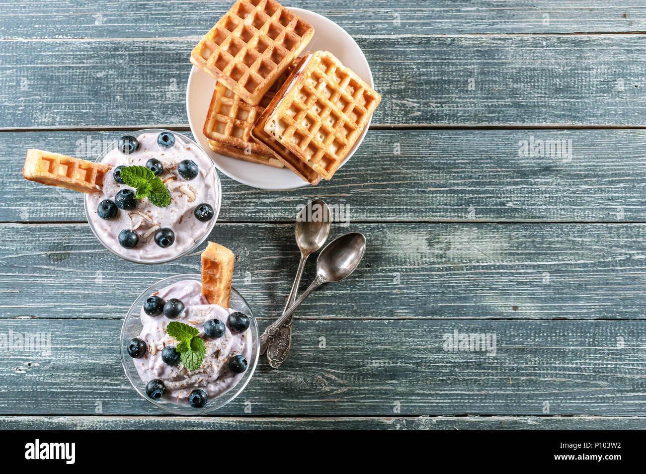 Curd dessert with blueberries in a glass cup and homemade Viennese waffles on a wooden background. Top view. Copy space Stock Photo