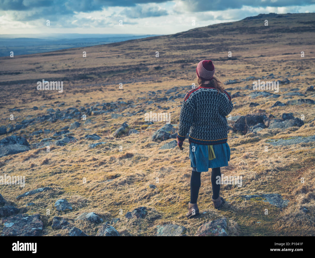 A young woman is walking on the moor in winter - Stock Image