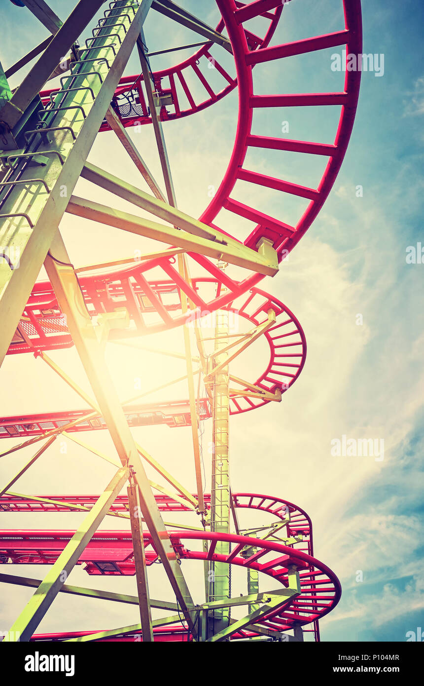Vintage stylized picture of roller coaster tracks in an amusement park at sunset. - Stock Image