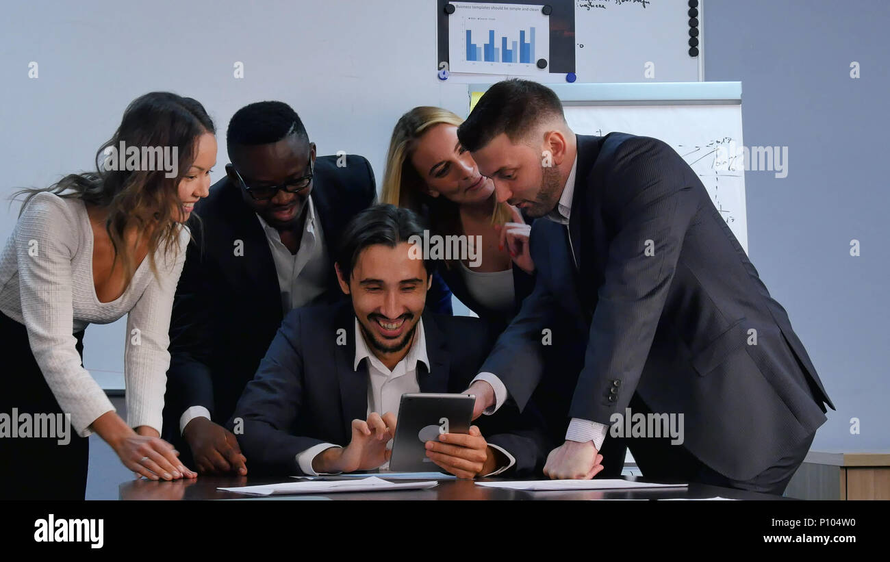 Positive business people working with digital tablet in office - Stock Image