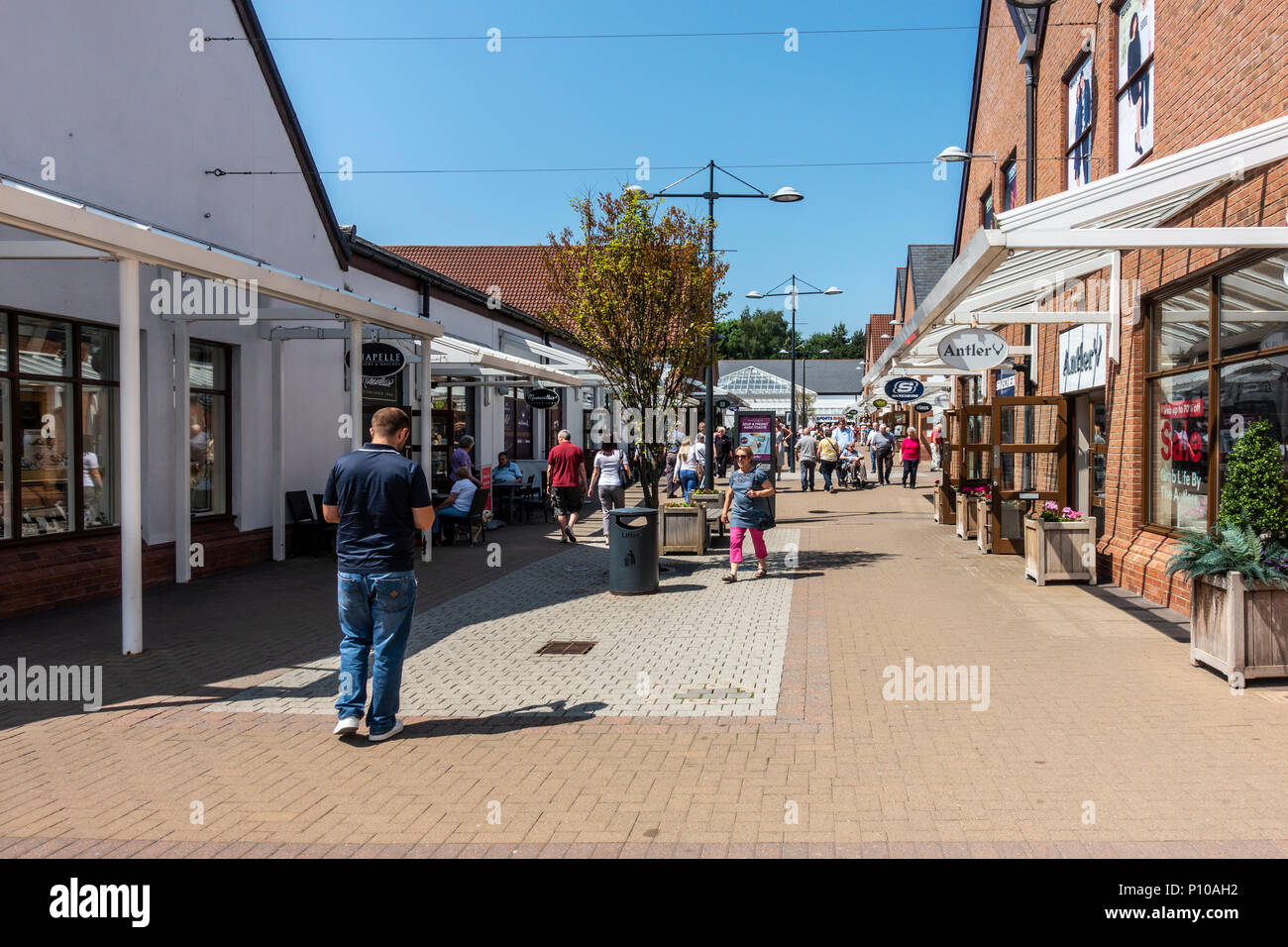 Shoppers on a sunny day at Gretna Gateway Outlet Village, a 'strip mall' in the very south of Scotland. - Stock Image