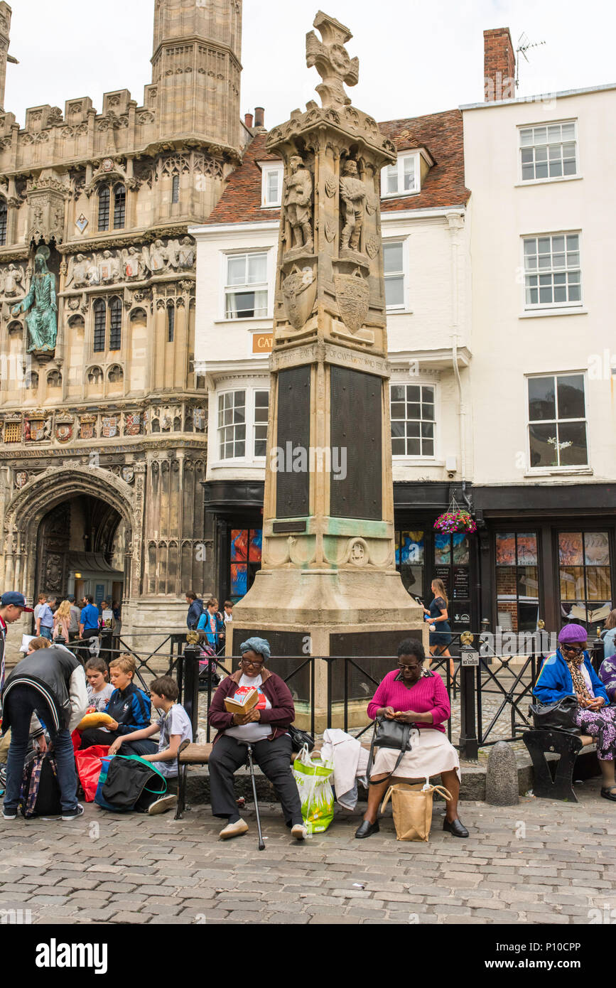 Tourists resting beside the First World War Memorial and the Christchurch Gate, Canterbury, England, UK. - Stock Image
