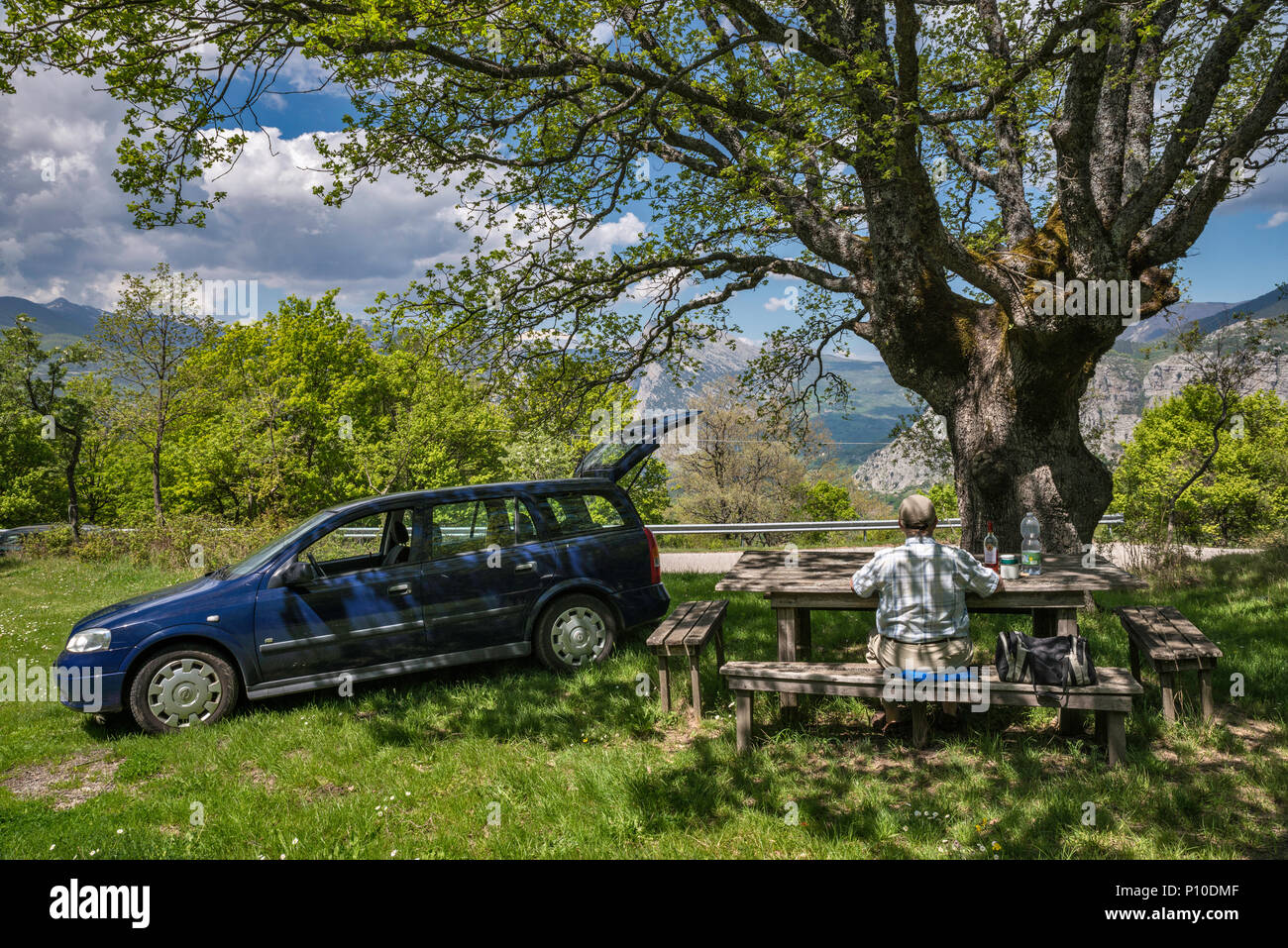 Man in his 60s picnicking at roadside table near town of San Lorenzo Bellizzi, Southern Apennines, Pollino National Park, Calabria, Italy - Stock Image
