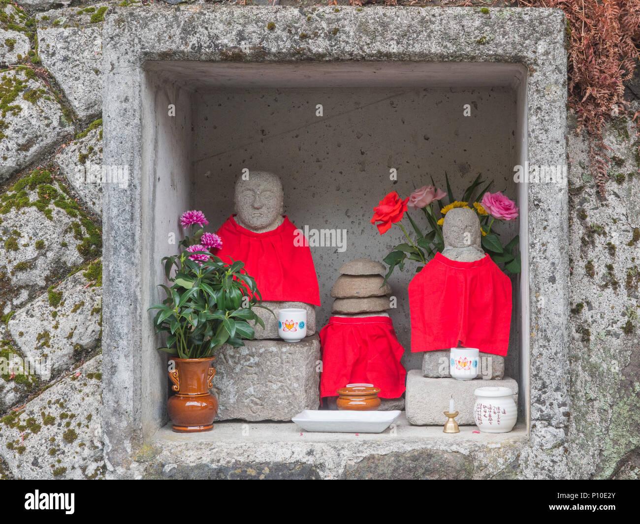 Japanese religion. A roadside shrine,  with buddhist deities wering red bibs, Ehime, Shikoku, Japan - Stock Image