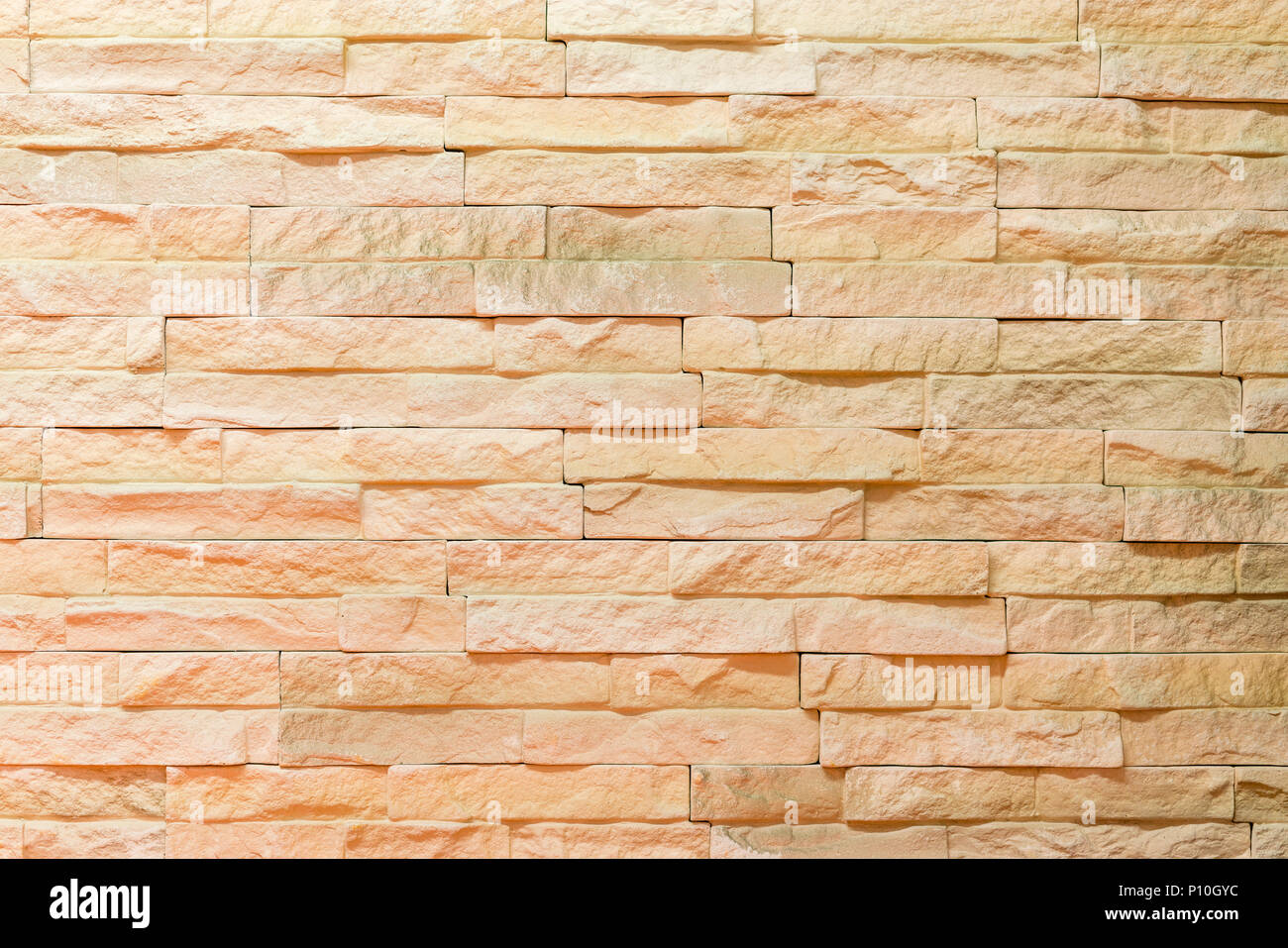 Wall made of decorative light brown stone. Decorating for the ...